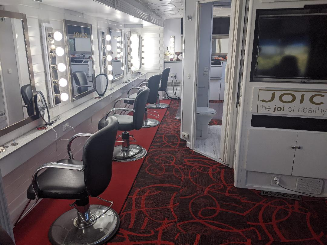 Inside mobile hair salon with black chairs